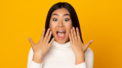 Wow. Surprised asian girl shouting over yellow background