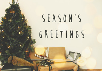 Season's greetings text sign on christmas tree in golden lights bokeh with festive stylish gifts in white room. Seasons greeting card