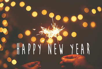 Happy New Year text sign on glowing sparkler in hands on background of golden christmas tree lights in dark festive room. Fireworks burning. Seasons greeting card