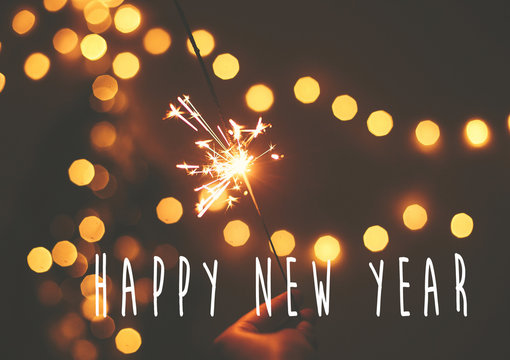 Happy New Year text sign on glowing sparkler in hand on background of golden christmas tree lights in dark festive room. Fireworks burning. Seasons greeting card