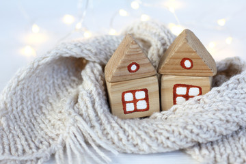 pair of wooden houses wrapped in a scarf, comfortably overwintering . Warming meeting christmas holidays