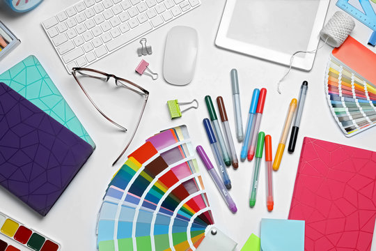 Flat lay composition with color palette and stationery on white background. Designer's workplace