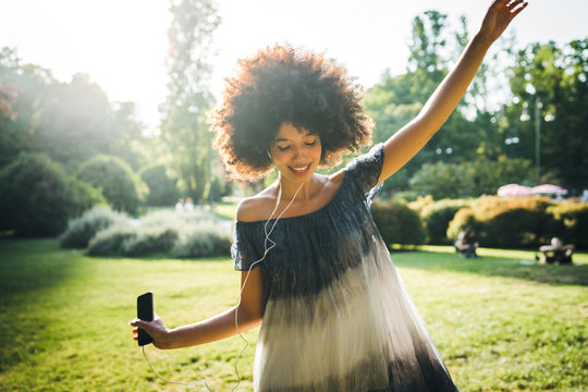 Young black woman dancing listening to the music with earphones from the smart phone in a park at sunset on a summer day