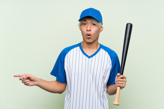 Young asian man playing baseball over isolated green background surprised and pointing side