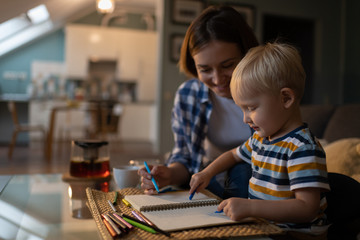 Little boy and female babysitter drawing picture with pencils at home