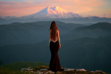 A beautiful young girl with a naked back is standing in an evening dress in the mountains of the Caucasus while admiring the sunset. girl looks at a sleeping volcano covered in snow and ice