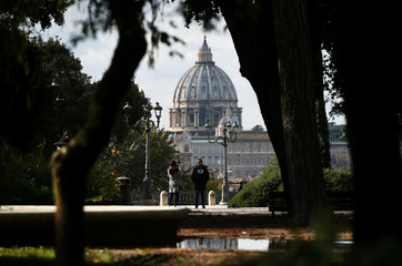 A woman takes a picture with the dome of Saint Peter's Basilica in the background from Pincio terrace in Rome