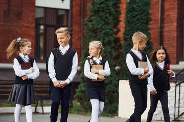 Group of kids in school uniform that is outdoors together near education building