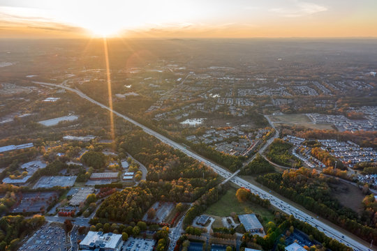 Aerial view Atlanta suburbs next to highway 400 during the Fall in the Golden hour with Sun Rays