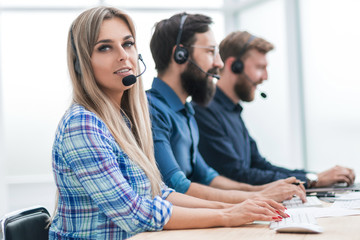 young woman with colleagues working in the office of the call center.