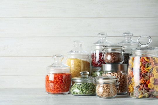 Glass jars with different types of groats and pasta on white wooden table