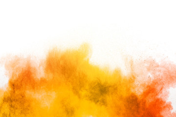 Abstract yellow orange powder explosion on white background. Freeze motion of yellow orange dust...