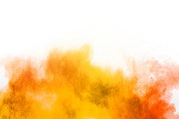 Abstract yellow orange powder explosion on white background. Freeze motion of yellow orange dust particles splash. Fototapete
