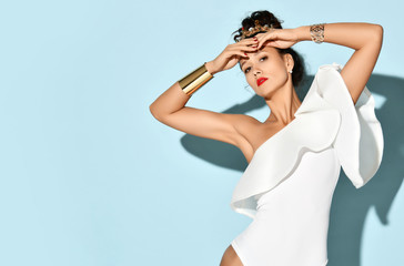Beautiful curly girl in a white glamorous bodysuit and a golden crown. Stylish fashionable summer trends