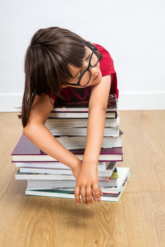 exhausted intellectual child relaxing, sleeping, leaning on pile of books