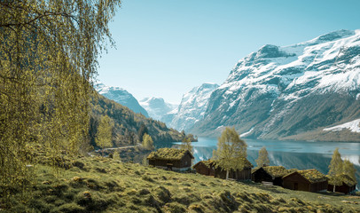 Beautiful norwegian landscape with old farm, lake and mountains