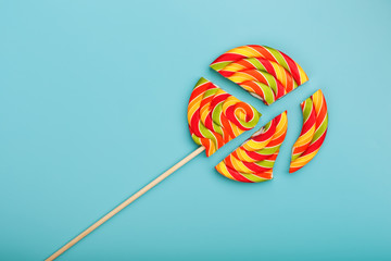 Lollipop broken into pieces on blue background, top view with copy space.