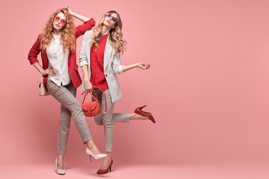 Fashionable woman with stylish hairstyle, makeup dance. Two Shapely blonde redhead girl having fun, trendy red outfit, heels, fashion hair, make up. Excited model, beauty dancing fun concept on pink