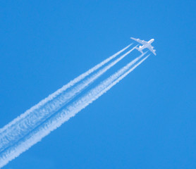 Wall Mural - Passenger plane flying high in the blue sky