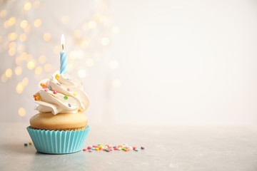 Birthday cupcake with candle on light grey table against blurred lights. Space for text Papier Peint