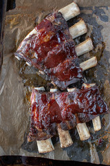 beef short ribs with barbecue sauce on baking tray flat lay
