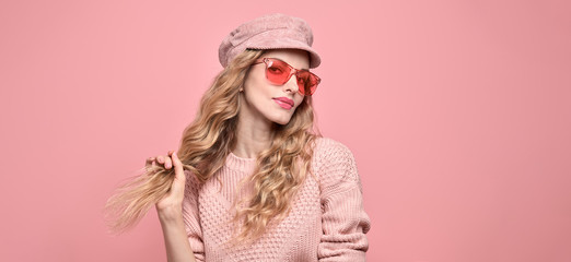 Fashionable lovable woman in Trendy pink outfit, stylish hairstyle, makeup smiling. Young blonde in jumper. Sensual beautiful model girl in stylish sunglasses, pastel fashion beauty banner on pink