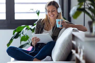 Pretty young woman listening to music with her digital tablet while drinking cup of coffee on sofa...