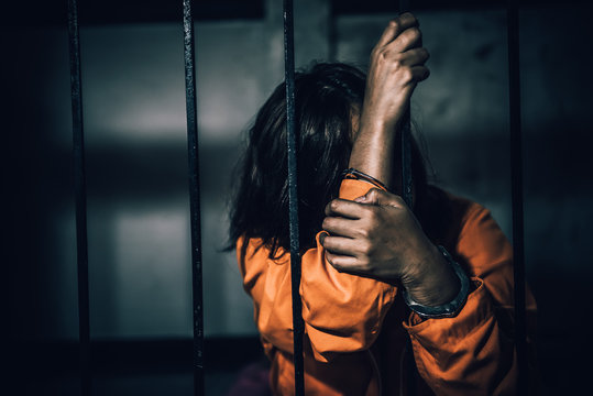 Portrait of women desperate to catch the iron prison,prisoner concept,thailand people,Hope to be free,If the violate the law would be arrested and jailed.
