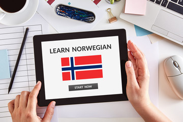 Hands using tablet with learn Norwegian concept on screen