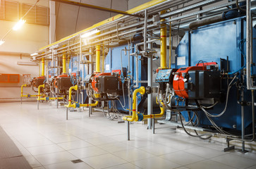 Modern industrial gas boiler room equiped for heating process. Heating gas boilers in a row, pipelines, valves.