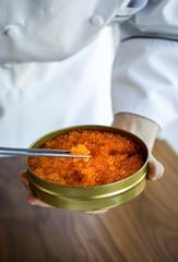 Chef holding tin of caviar