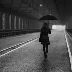 Girl under old bridge in the rain