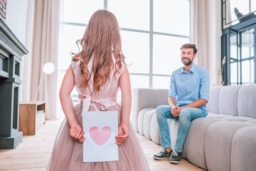 small girl holding picture of the heart behind her back while father sitting on the couch at home