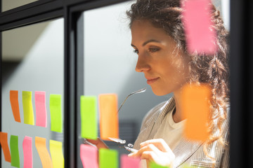 Thoughtful young female boss team leader looking at kanban board.