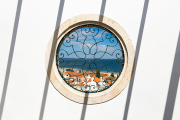 Looking through a circular window at Lisbon