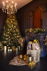 Interior of luxury modern living room with fireplace, comfortable sofa and chandelier decorated with golden Christmas tree and gifts