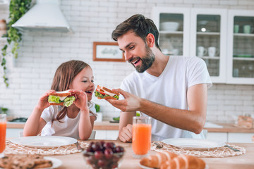 dad feeding girl eating with his sandwich for breakfast on the kitchen