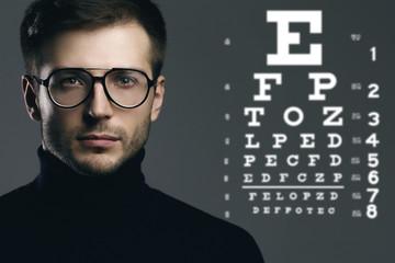 Man wearing eyeglasses and eye chart