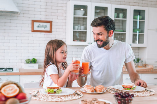 smiling father and daughter clicking glasses with drinking juice for breakfast in the kitchen