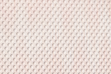 Beige plastic surface with round holes pattern texture and background