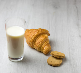 A croissant, some cookies and a glass of milk