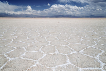 Panoramic of cracked ground with mountains in the background in the salt flats in the Salinas Grandes in Jujuy, Argentina