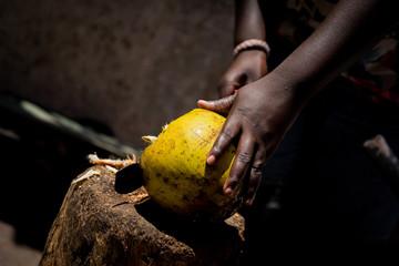A man chops a coconut with a machete