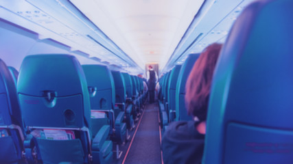 Blured Interior of airplane with passengers on seats and stewardess walking the aisle.