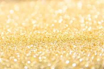 Defocused gold glitter background. Gold abstract bokeh background. Christmas abstract background.
