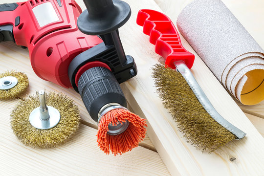 Drill, sandpaper and abrasive brushes with nylon and metal wire on a wooden surface. Tools for cleaning, polishing and grinding of wood and metal.