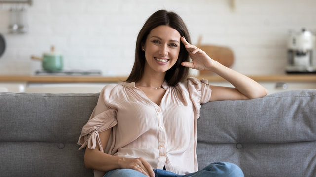 Happy 30s woman sitting on cozy sofa in living room.