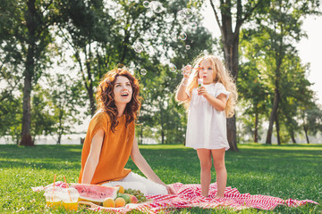 little girl blowing soap bubbles while mother sitting on picnic blanket in the park