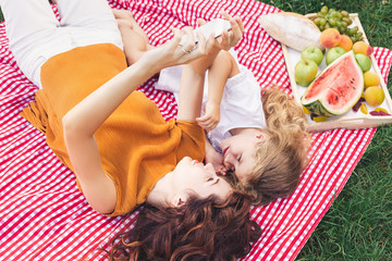 mother and daughter taking selfie on smartphone while lying on the picnic blanket in the park, overhead view