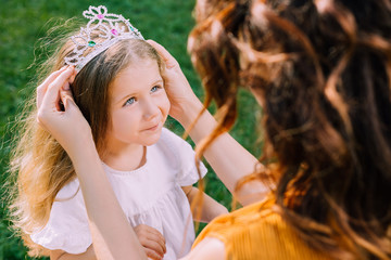 mommy putting crown on daughter's head, close up